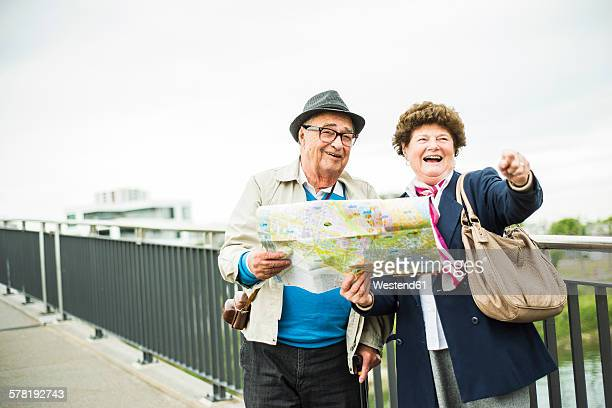 Senior couple with map standing on a bridge