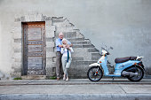 Romantic senior couple (60s) taking a break, travelling by motor scooter.