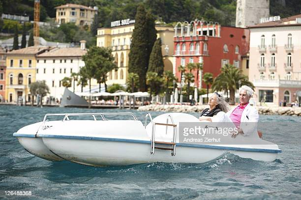 Senior couple with pedal boat on water, Italy