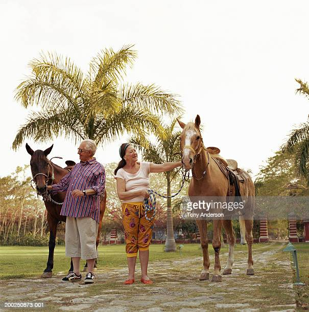 Senior couple with saddled horses
