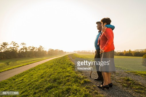 Senior couple with walking sticks standing in the nature