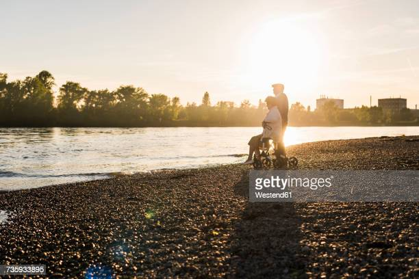 Senior couple with wheeled walker on the beach at sunset