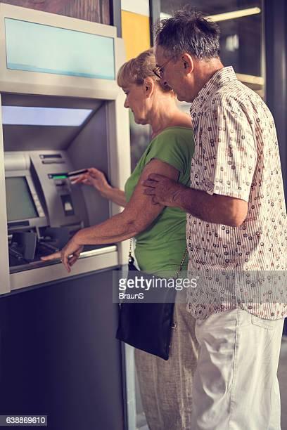 """couple de personnes âgées de retirer de l """"argent à un distributeur automatique de billets."""