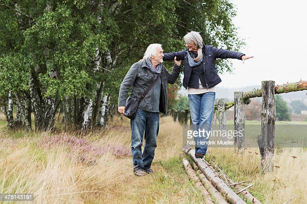 Senior couple, woman balancing on logs