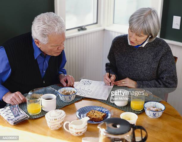 Senior couple working on crossword puzzle over breakfast