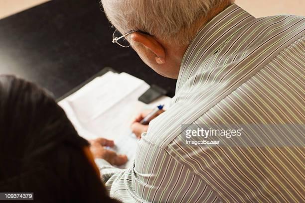 Senior couple writing document in living room