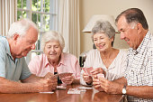 Group Of Senior Couples Enjoying Game Of Cards At Home Laughing