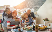 Senior couples having fun at barbecue dinner in home terrace - Pensioner friends having cute tender moments at bbq meal - Focus on right man - Love and jouyful elderly lifestyle concept