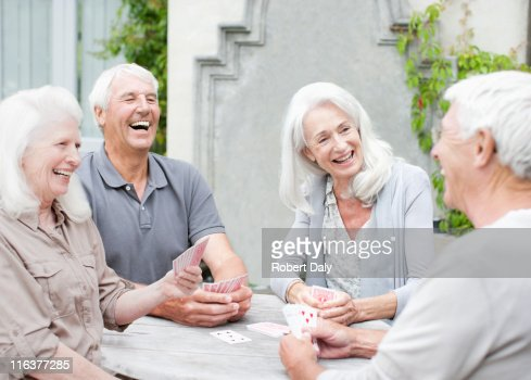 Senior couples playing cards on patio : Stock Photo