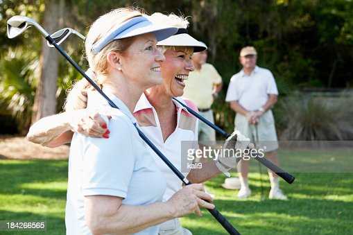 Senior couples playing golf.