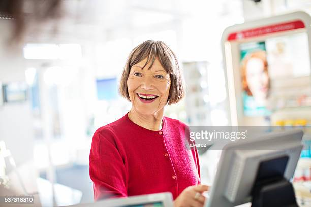 Senior customer standing at pharmacy checkout counter