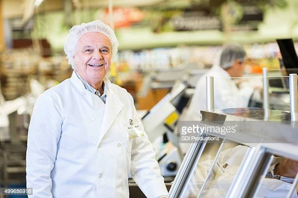 Senior deli manager smiling while working in supermarket