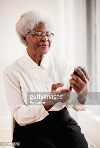 Senior diabetic woman tests her blood sugar : Stock Photo