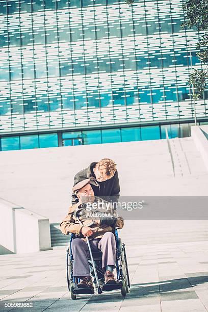 Ältere Behinderte Mann im Rollstuhl und Enkel im Freien, Europa