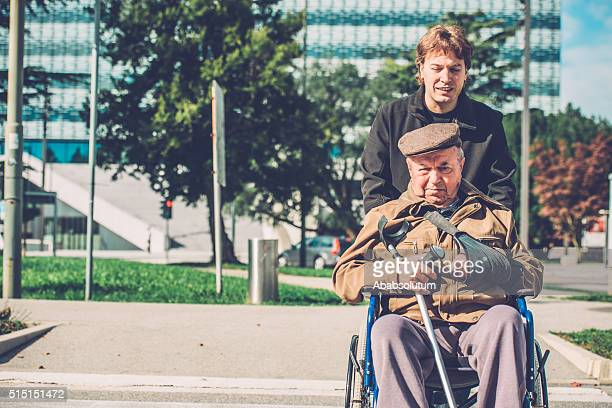 Senior Disabled Man in Wheelchair and Grandson Outdoors, Europe