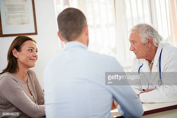 Senior doctor having consultation wit mid-adult couple
