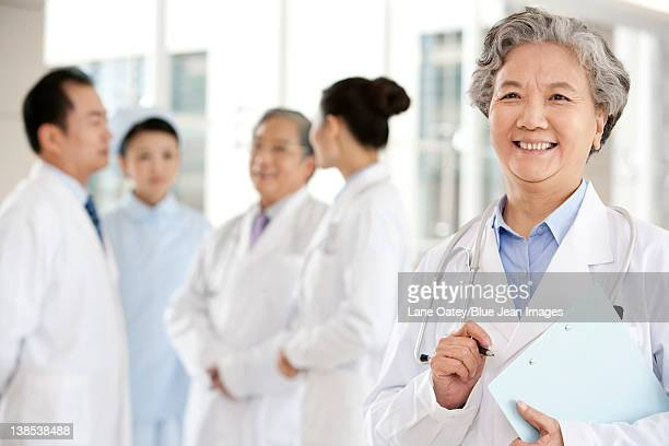Senior Doctor in Forground with Clipboard, Doctors and a Nurse in Background