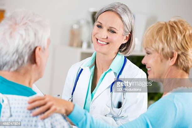 Senior doctor smiling while examining senior patient in hospital