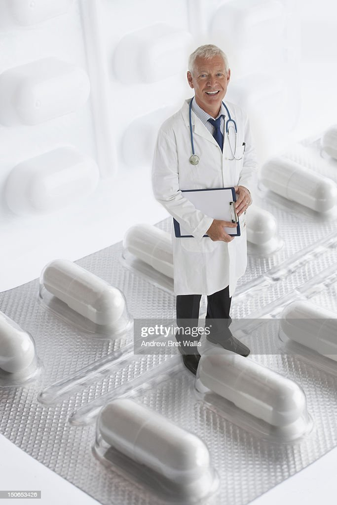 Senior doctor standing on prescription pills : Stock Photo