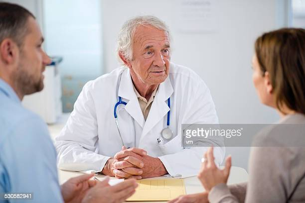 Senior Doctor with Mid Adult Couple