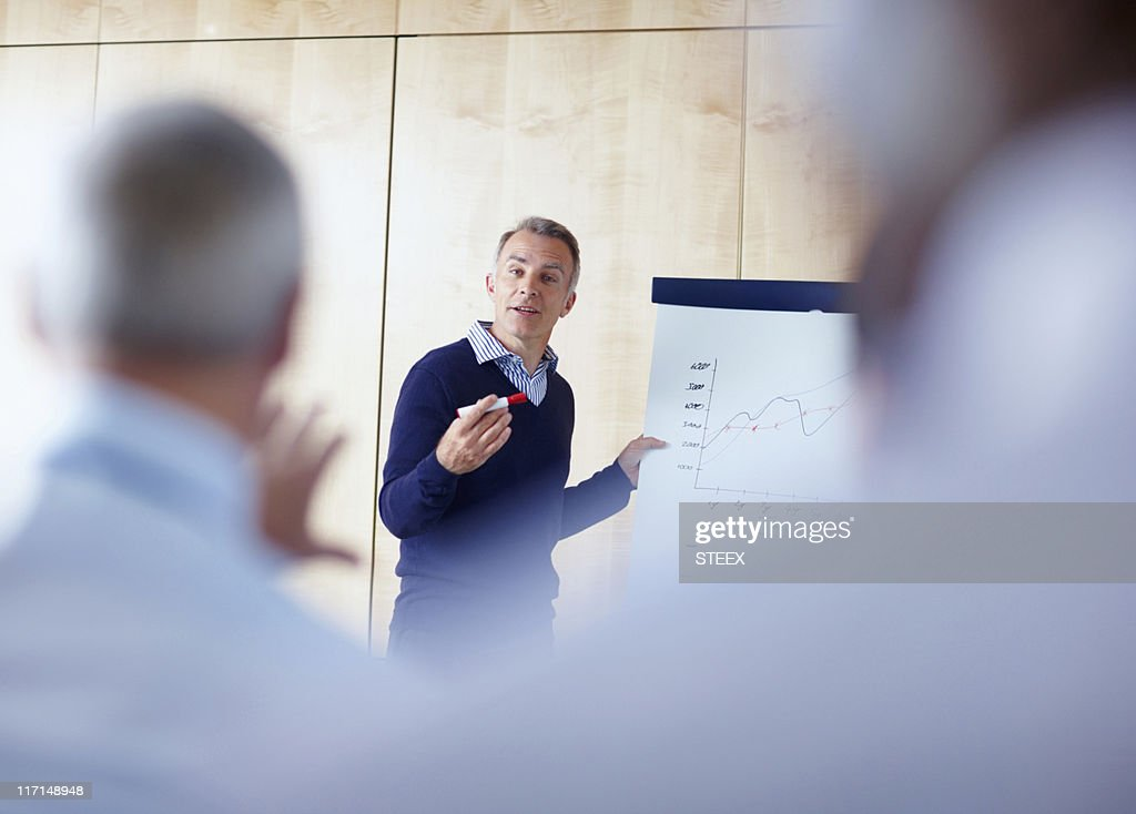 Senior executive giving presentation : Stock Photo