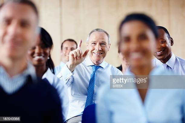 Senior executive raising his hand