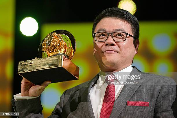 Senior Executive Vice President of Tencent and President of its Online Media Group Sy Lau holds its Media person of the year award during the Cannes...