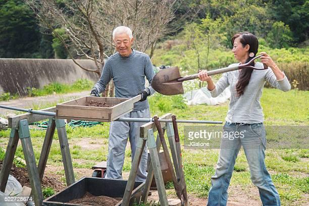 Senior Landwirt und seiner Tochter Durchsieben Boden