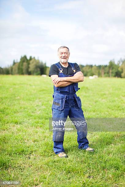 Senior farmer standing on field, Smaland, Sweden