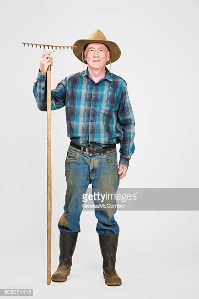 Senior farmer with rake full length
