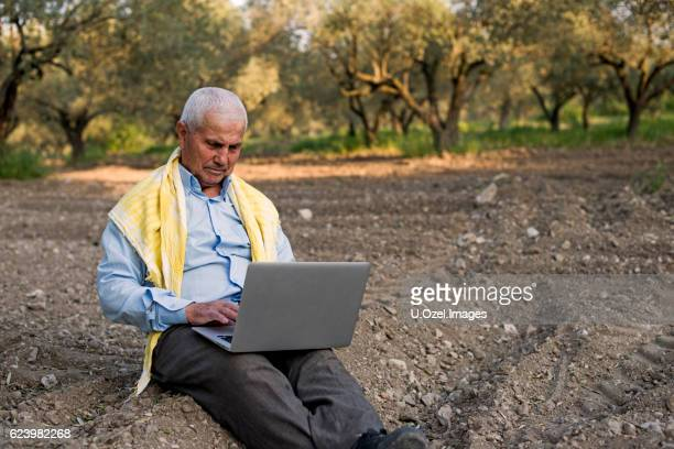 Senior Farmer With Their Laptop in The Field
