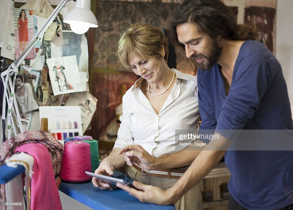 senior fashion designer in her studio with her son : Stock Photo