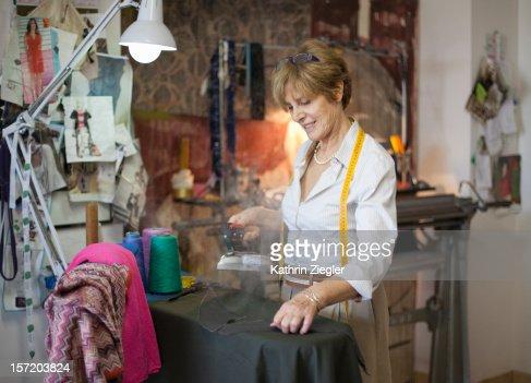 senior fashion designer ironing fabric : Stock Photo