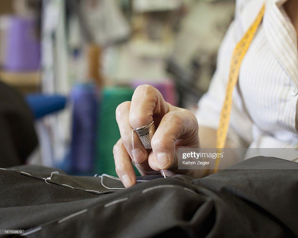 senior fashion designer sewing, close-up of hands