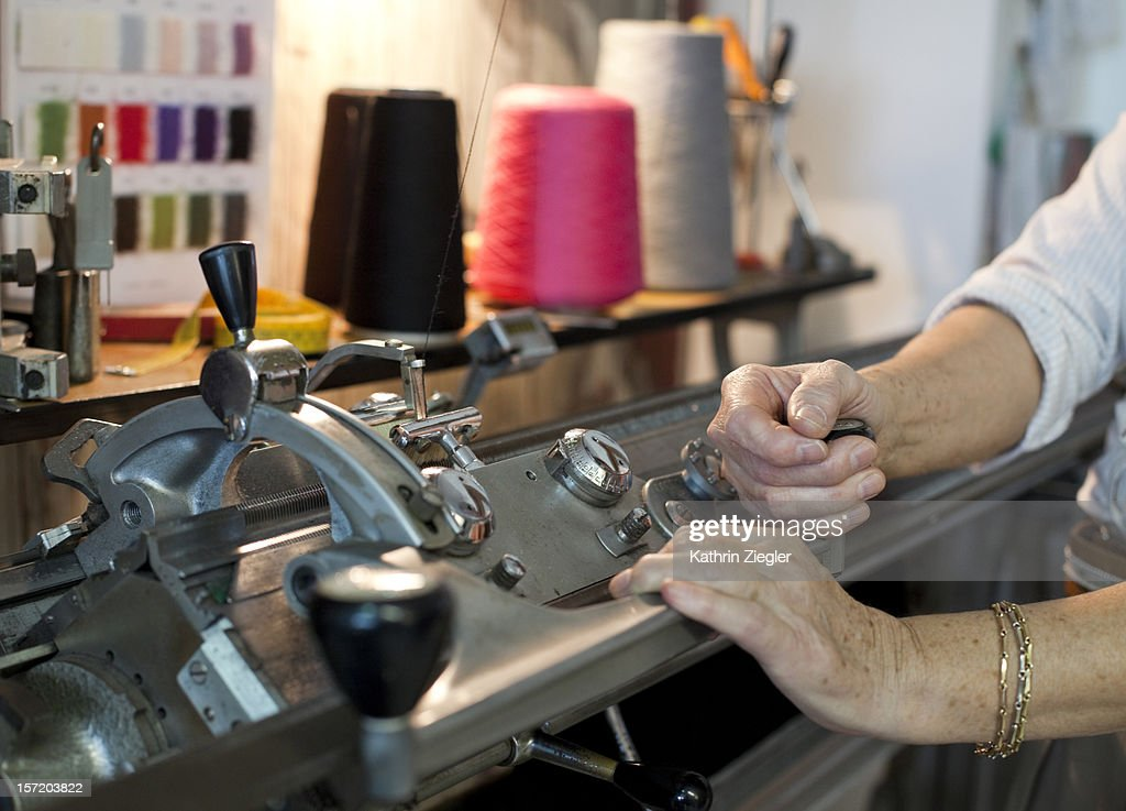 senior fashion designer using knitting machine : Stock Photo