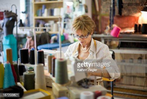 senior fashion designer using sewing machine : Stock Photo