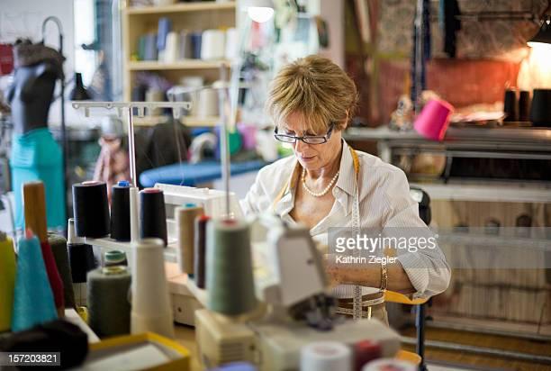 senior fashion designer using sewing machine