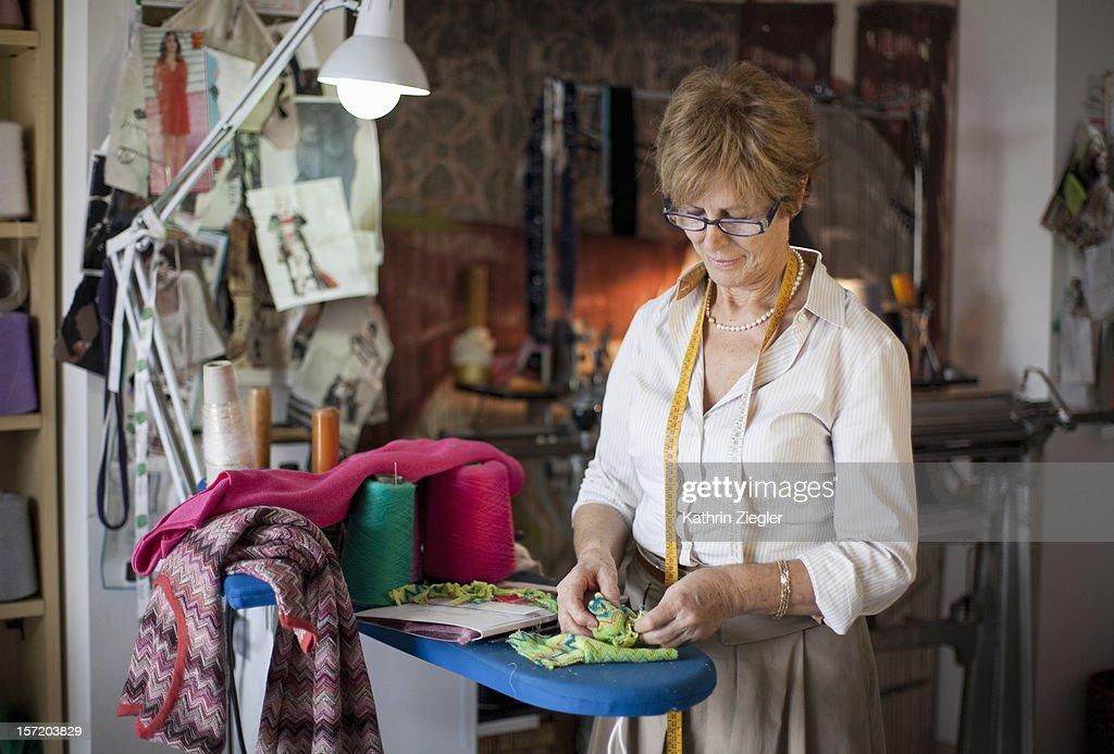 senior fashion designer working in her studio : Stock Photo