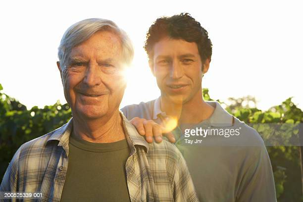 Senior father and mature son standing in vineyard, smiling, portrait