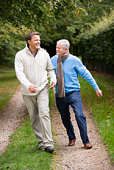 Senior father and son walking on path outdoors smiling