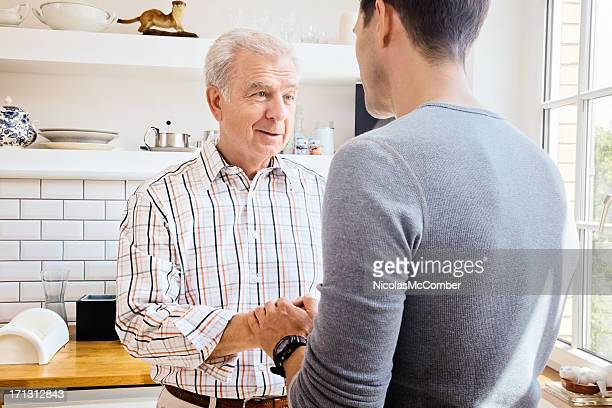 Senior father sharing good news with adult son in Kitchen