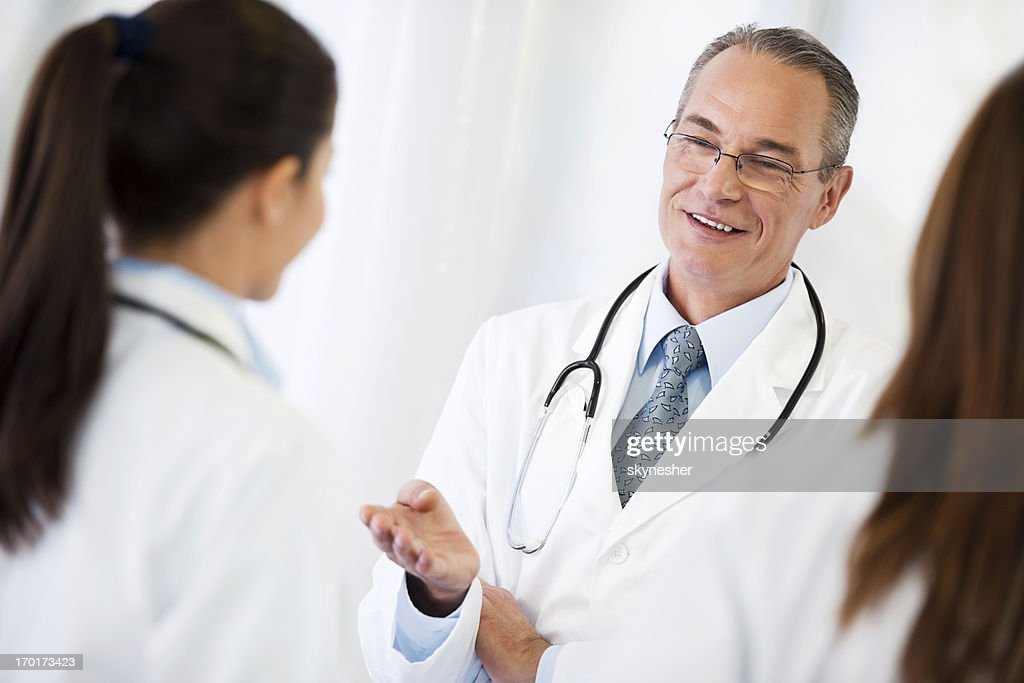 Senior fellow doctor gives advice to younger colleagues. : Stock Photo