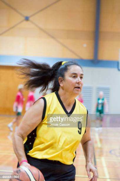 Senior female basketball player active on court with ball