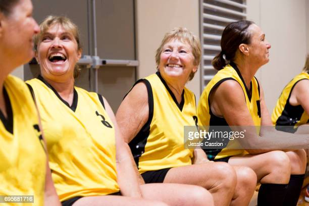 senior female basketball players laughing whilst sitting on bench in indoor court