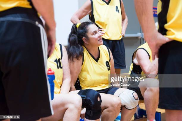 Senior female basketball players, sitting and standing, have team talk at side of indoor court