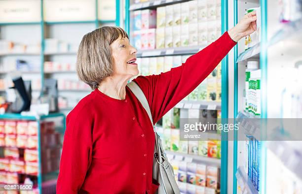 Senior female customer buying medicine