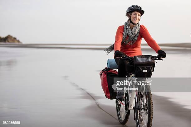 Senior female cycling along beach