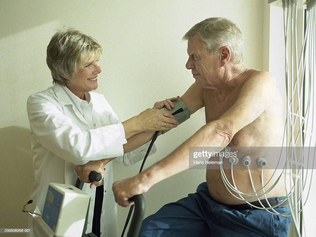 Senior female doctor by male patient having cardiology test