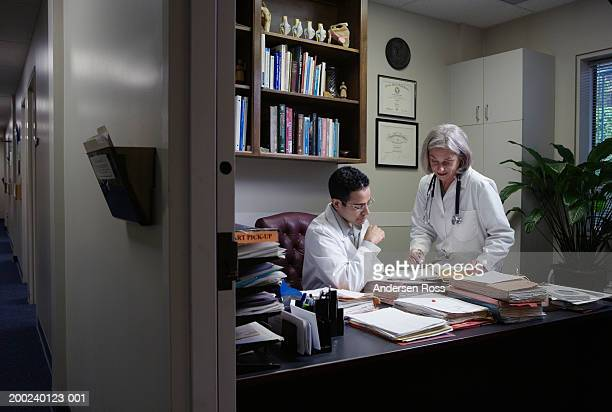 Senior female doctor discussing file with young male doctor in office