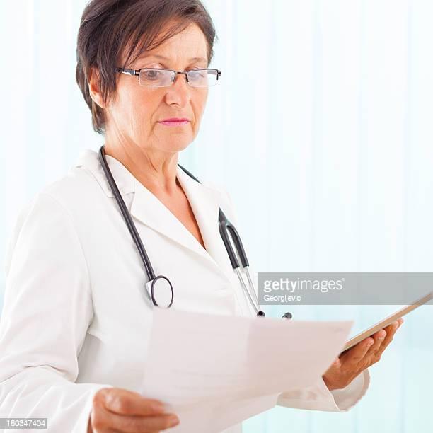 Senior weiblich Arzt medizinische Bericht lesen